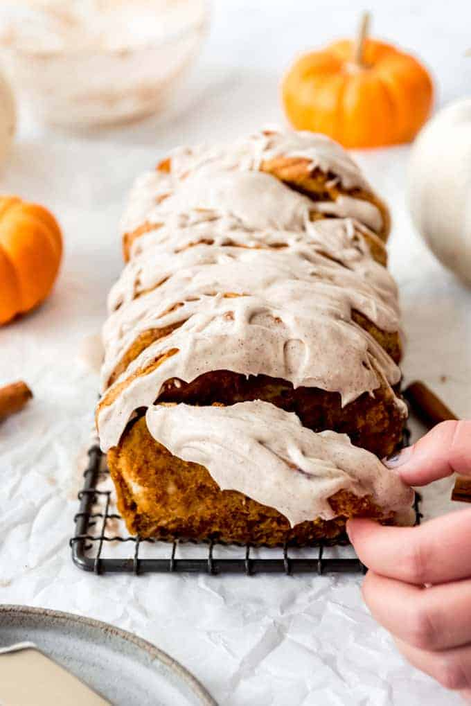 A hand pulling off a piece of pumpkin pull apart bread.