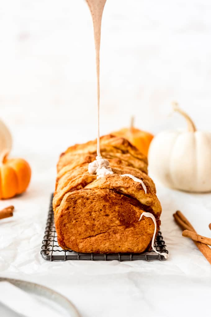 Glaze being drizzled over a loaf of pumpkin bread.