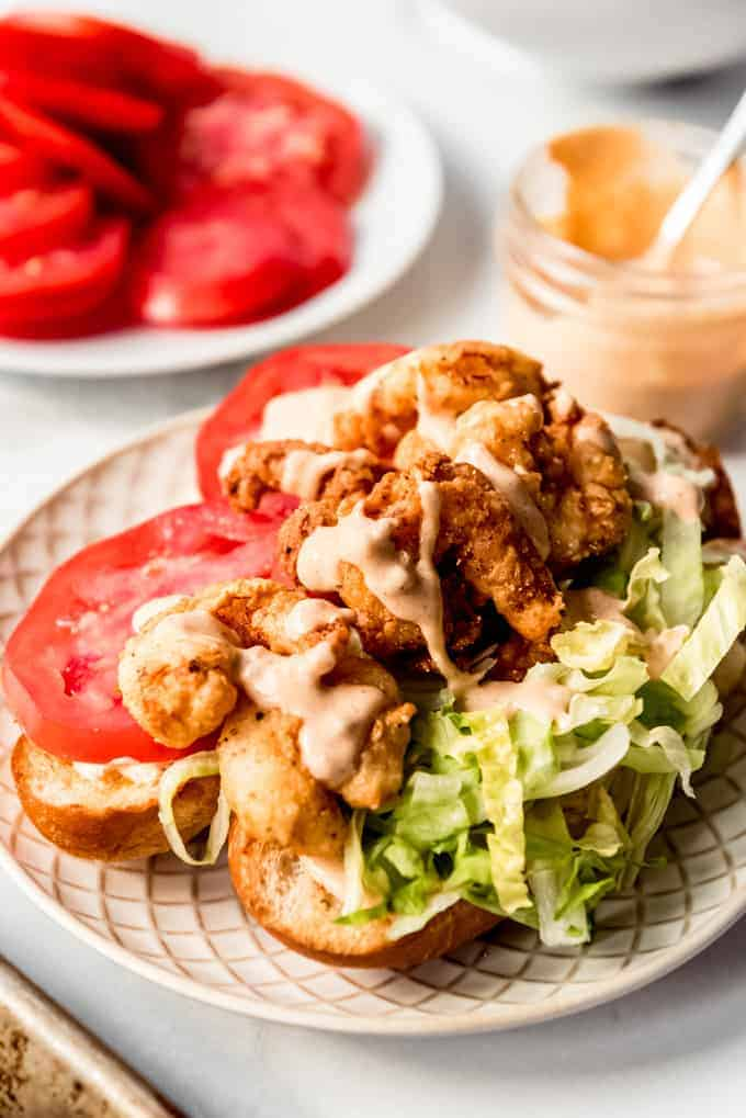 Shrimp po'boy on a plate topped with remoulade