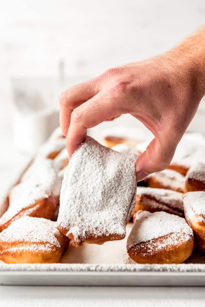 A hand picking up a beignet.