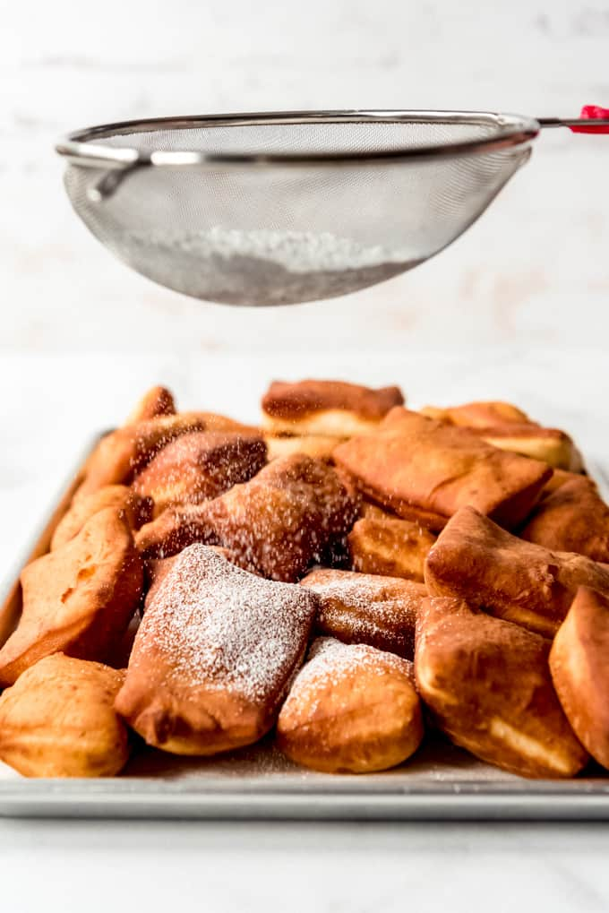 Powdered sugar being dusted over fried dough.