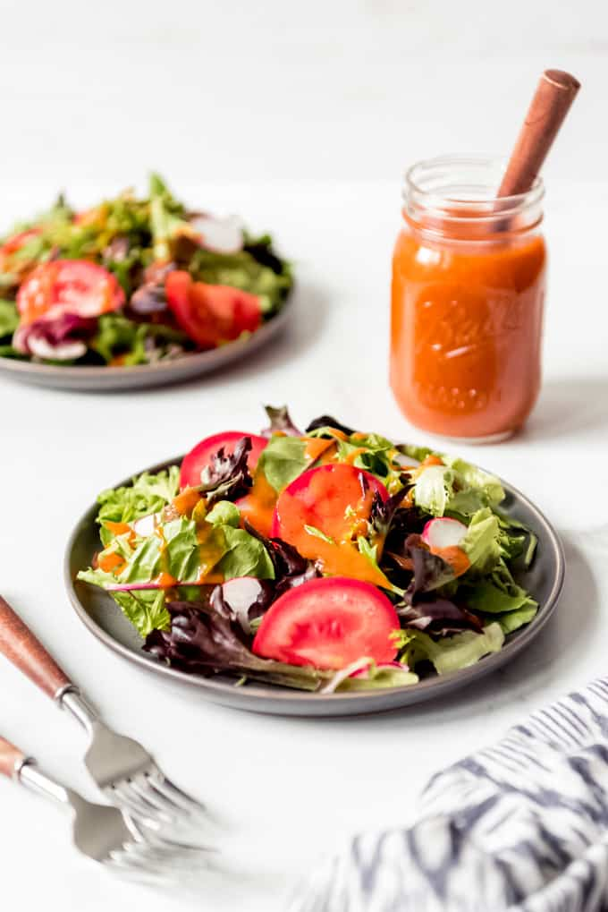 2 plates of salad and a jar of the sauce in the background