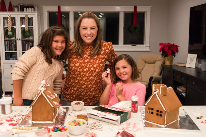 A mom and daughters decorating gingerbread houses.