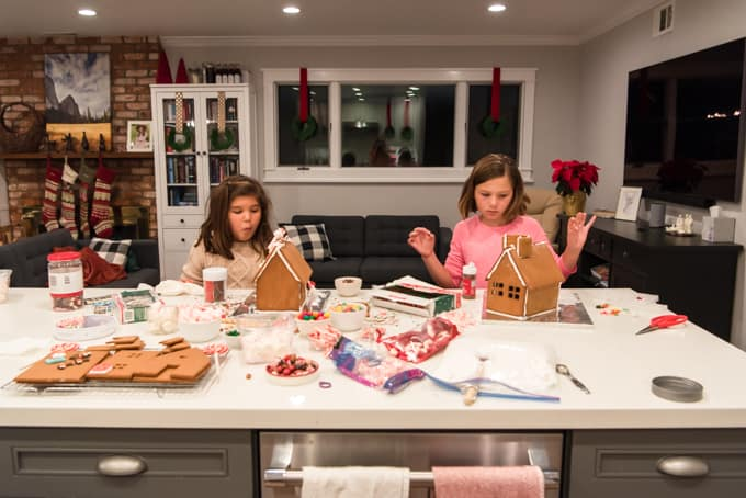 Kids decorating gingerbread houses.