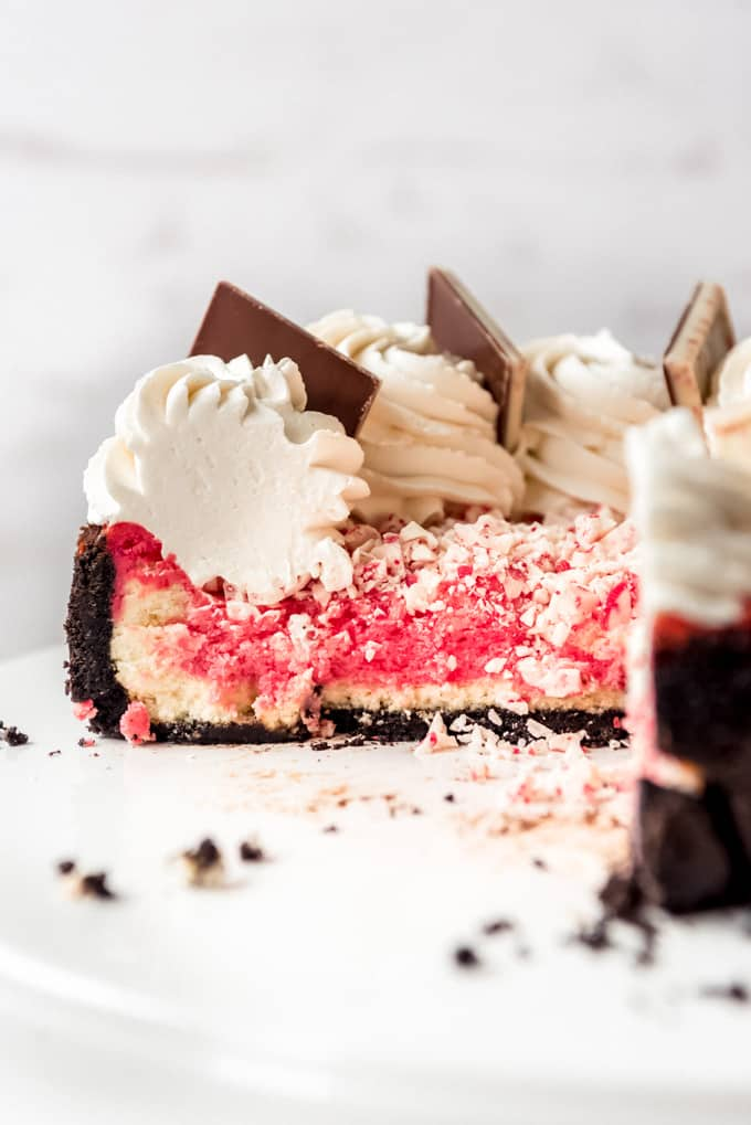 A sliced peppermint cheesecake on a white cake plate.
