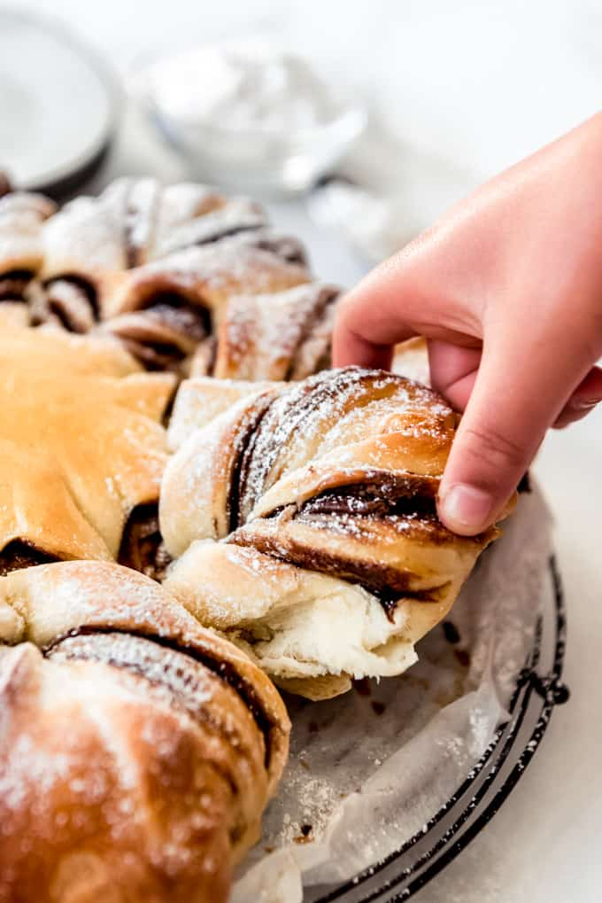 A hand pulling off a piece of twisted nutella sweet bread.