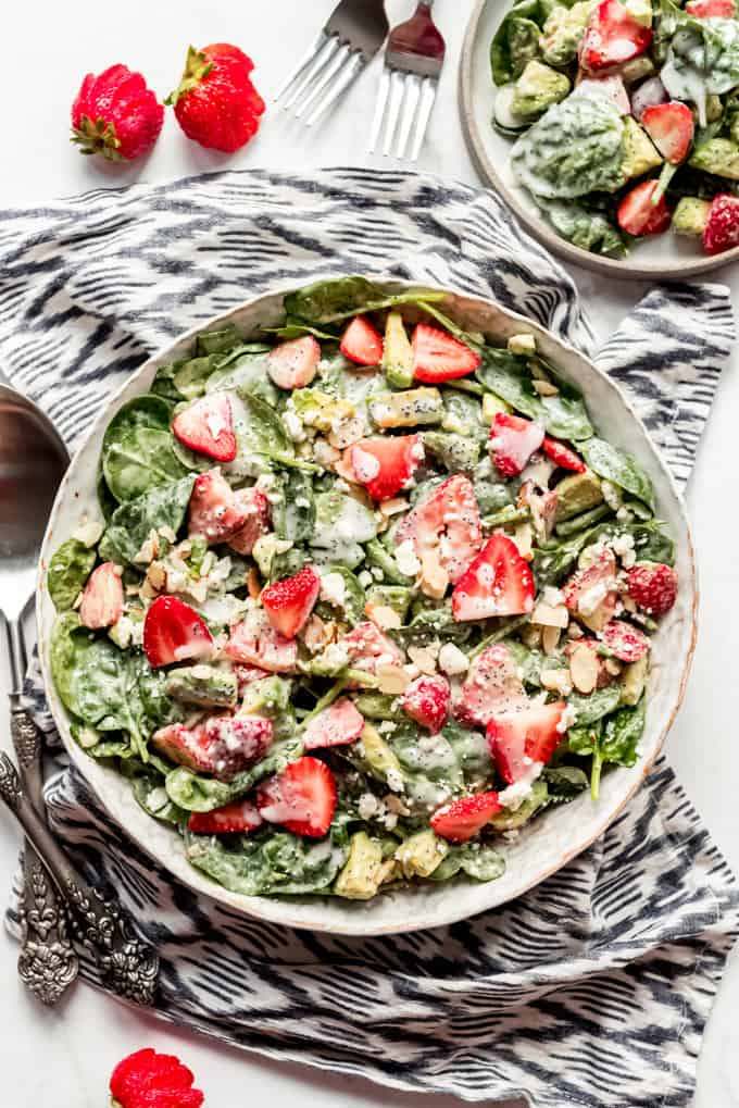A bowl of strawberry spinach salad on a cloth, with a portion to the side