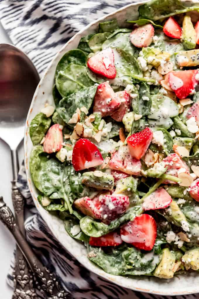 A bowl of strawberry spinach salad with silverware