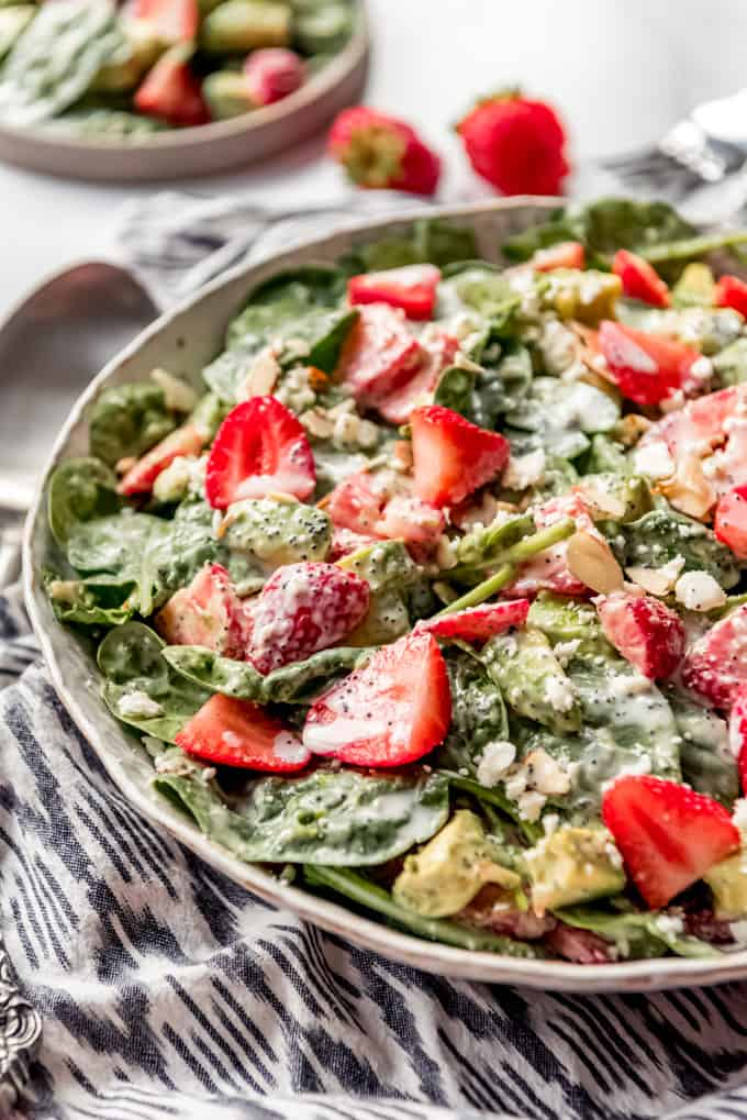 A bowl of strawberry spinach salad on a cloth