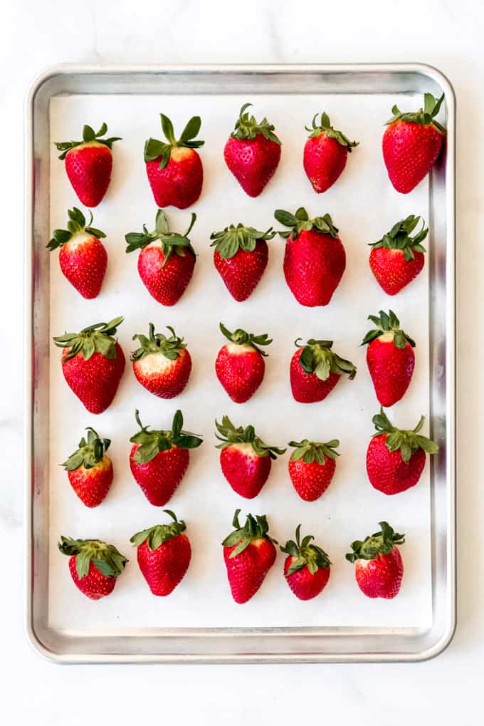 Washed strawberries lined up on a baking sheet.