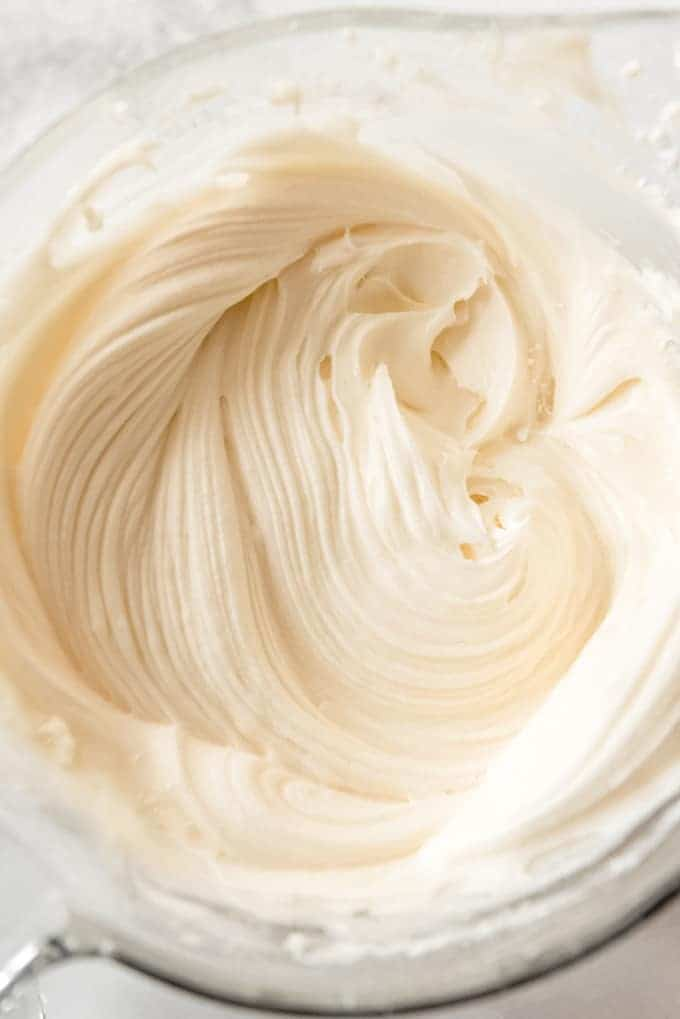 Overhead, freshly mixed cream cheese frosting in a glass measuring cup.