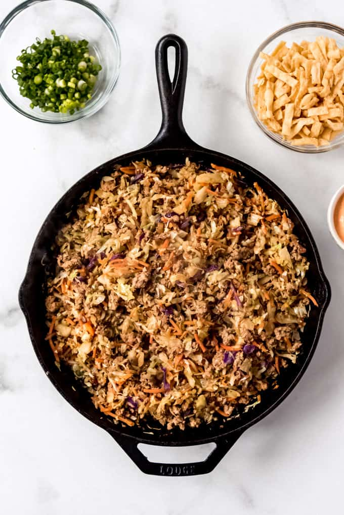 over head shot of Egg Roll in a Bowl in skillet surrounded by garnishes