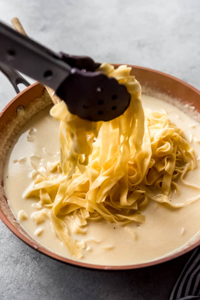 fettucine being added by tongs to the alfredo sauce