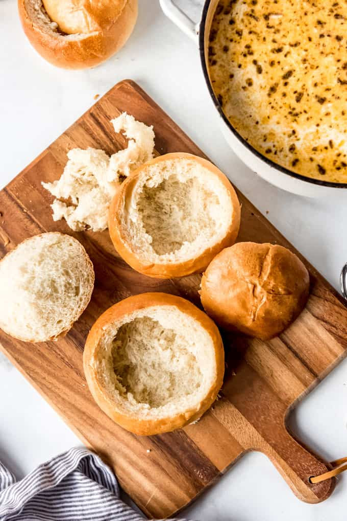 Homemade Bread Bowls on a wooden chopping board with tops at side