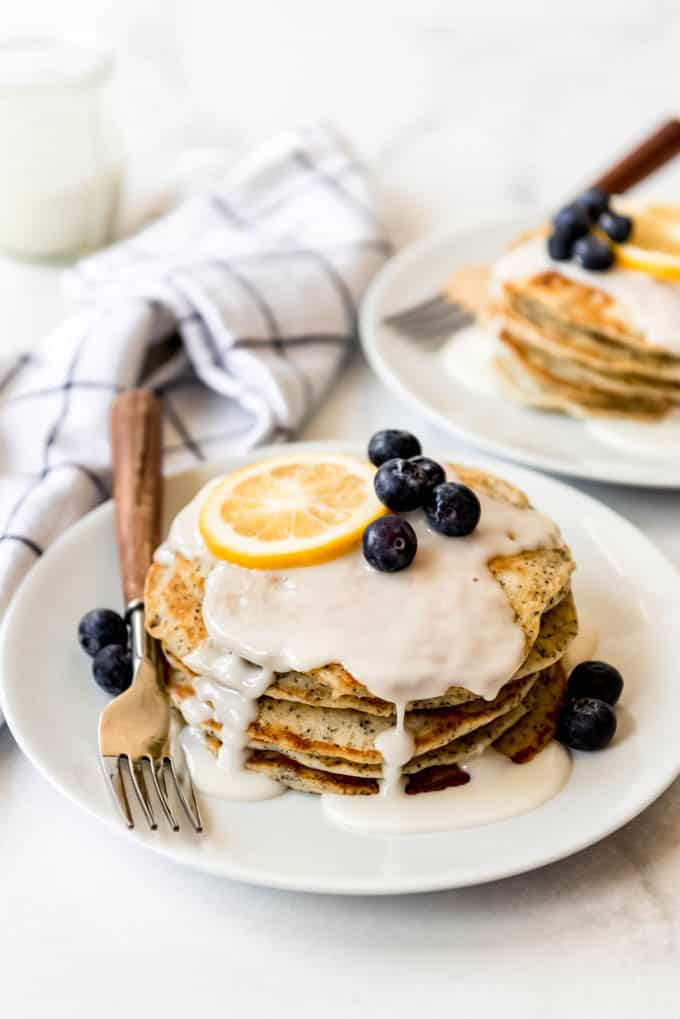 A stack of pancakes with lemon glaze and blueberries.