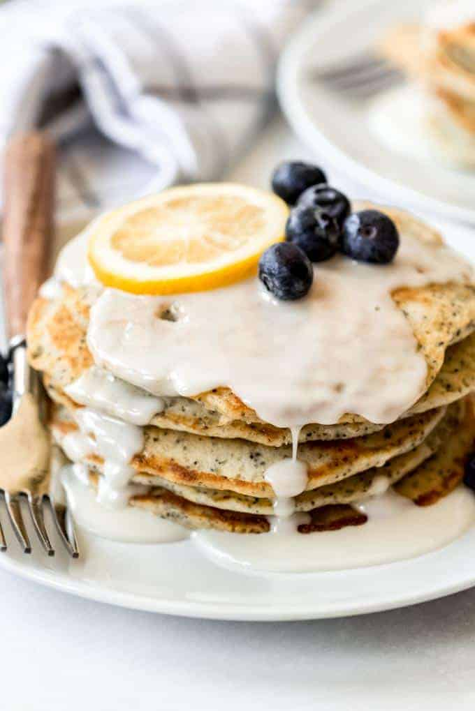 A stack of lemon poppy seed pancakes on a plate with lemon glaze on top.