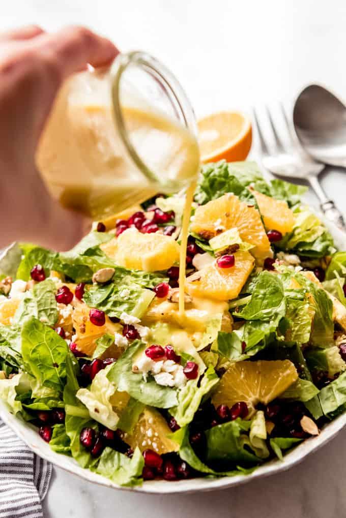 Orange vinaigrette being poured over Orange Pomegranate Salad