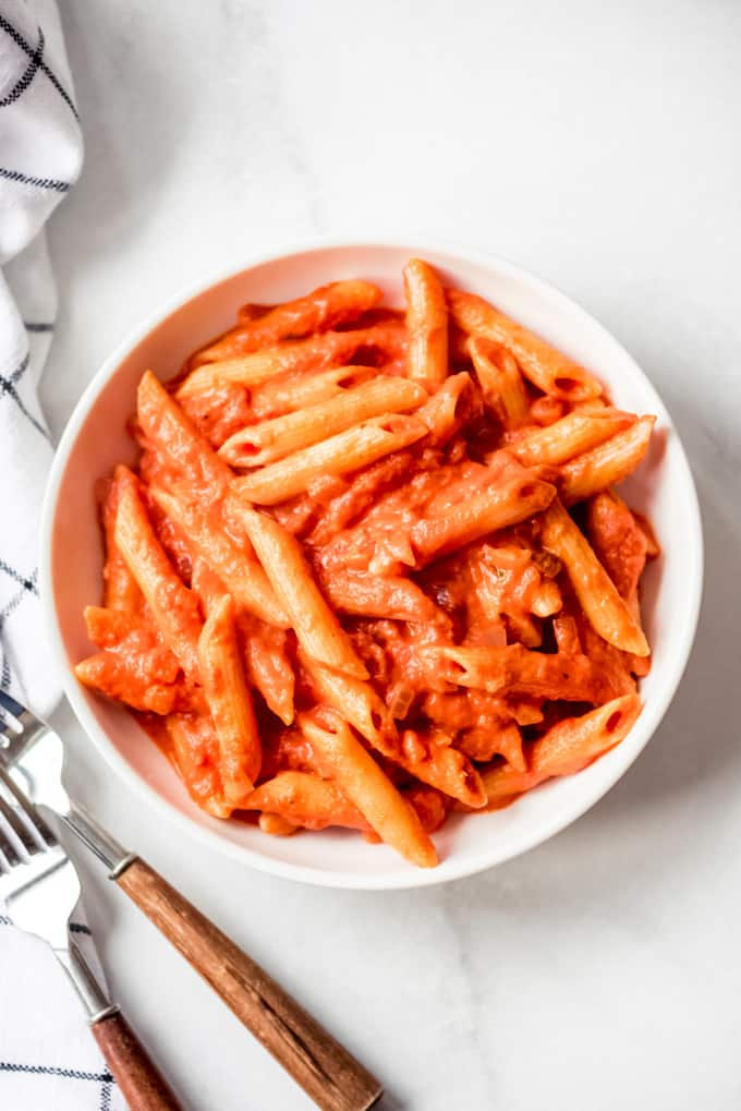 overhead shot of penne alla vodka in a bowl beside silverware