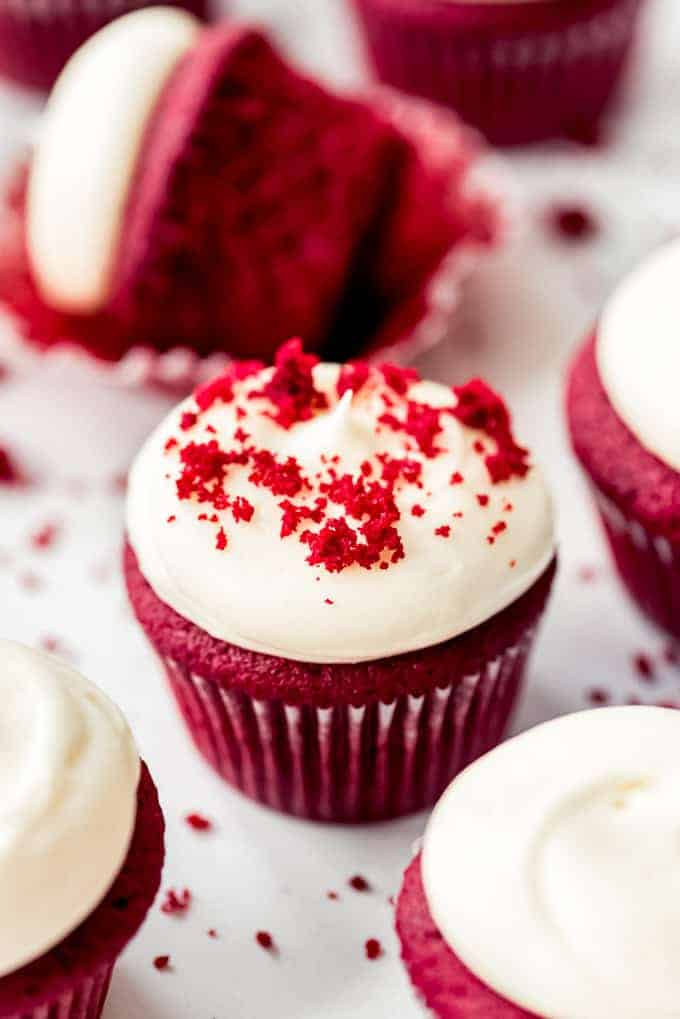 Red velvet cupcakes with frosting on marble counter with red velvet cake sprinkles
