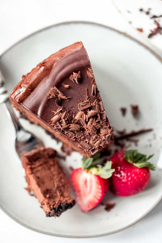 Triple Chocolate Cheesecake, bite on the fork, with strawberries