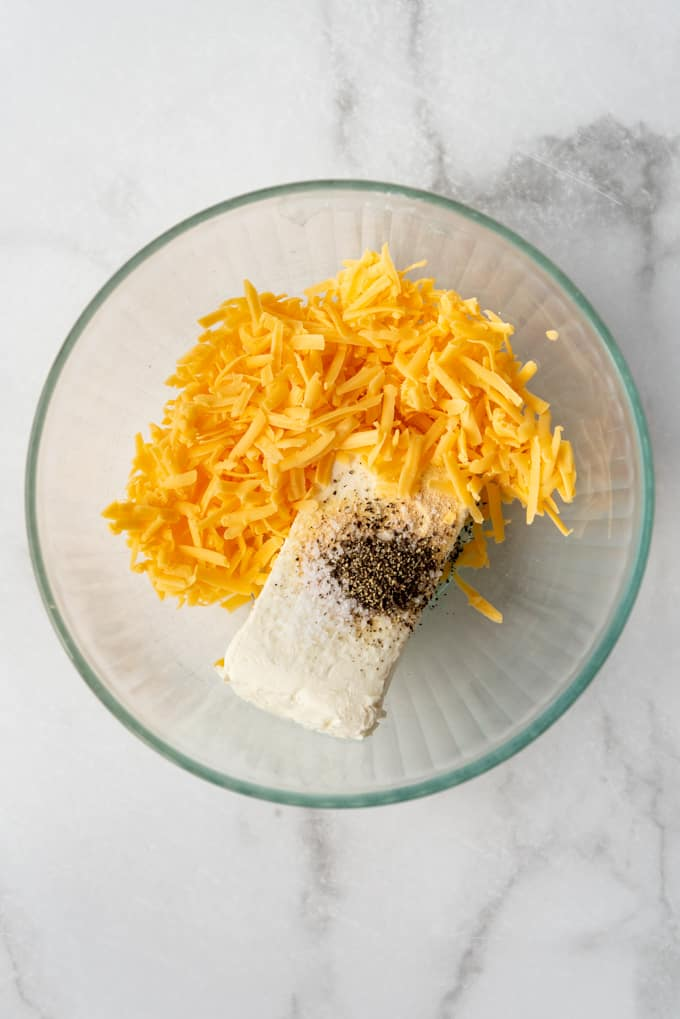A bowl with cream cheese, cheddar cheese, salt and pepper.