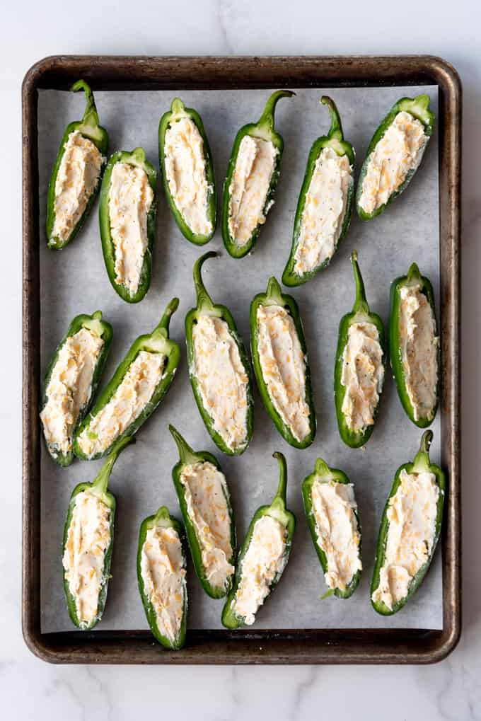 Jalapeno halves with cream cheese and cheddar cheese filling on a baking sheet.
