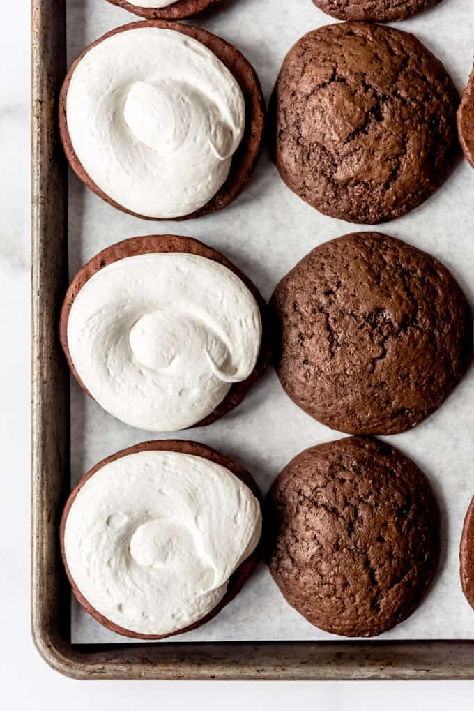 Chocolate cookies with marshmallow frosting piped on top.