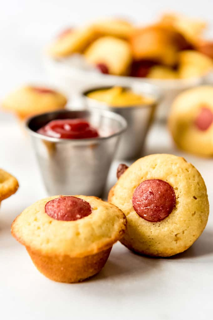 Mini corn dog muffins in front of cups of ketchup and mustard.