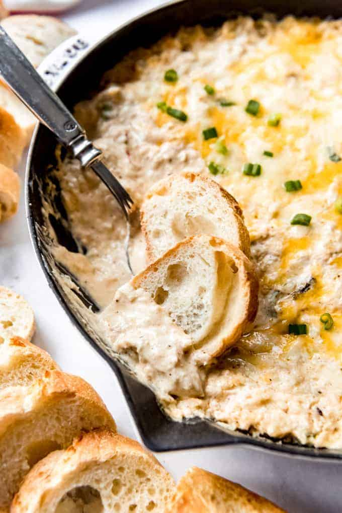 baguette slices in a skillet of hot crab dip