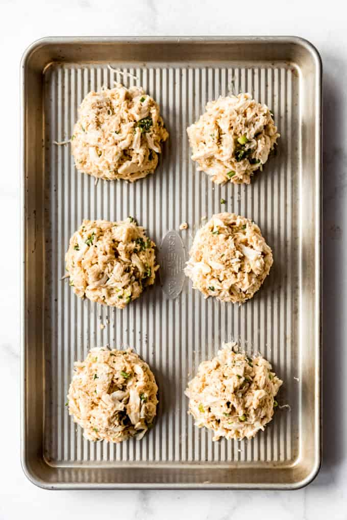 crab cake mounds on a baking sheet ready for the oven
