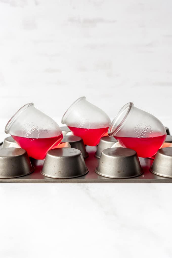 Glass cups filled with Jello set at an angle on a muffin pan.