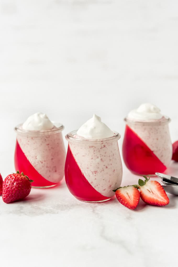 Dessert cups filled with strawberry jello and mousse.