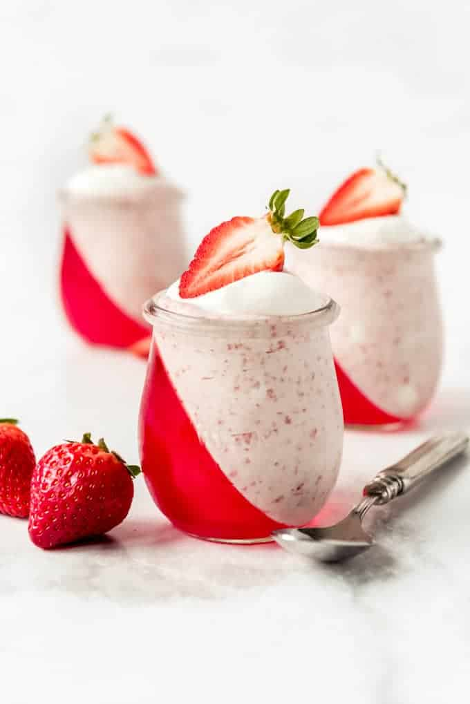 Strawberry jello set at an angle in dessert cups with mousse.
