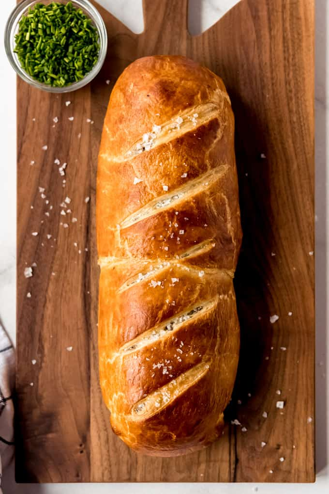 uncut beef wellington on wooden board, sprinkled with flaky salt.