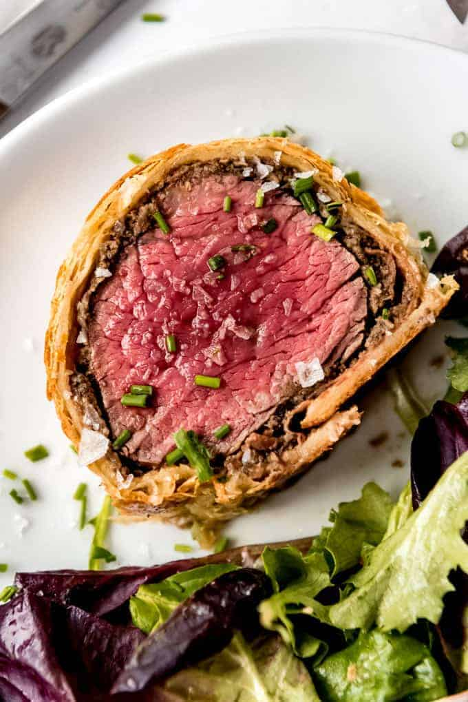overhead shot of beef wellington on white plate, garnished with chives and flaky salt next to salad.