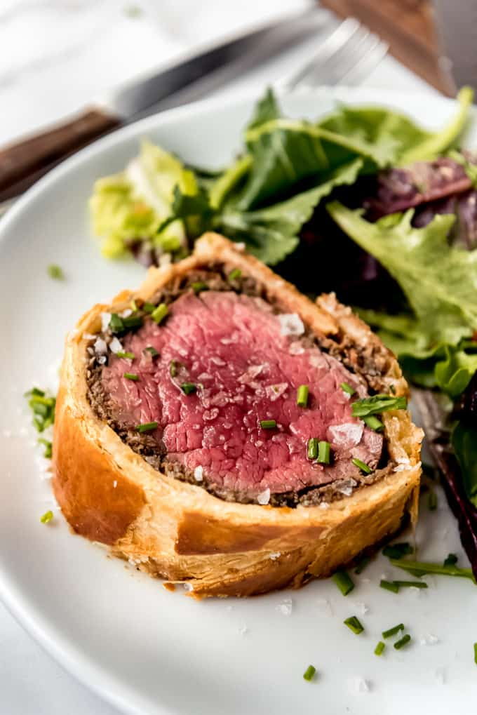 beef wellington served on a white plate with salad, garnished with chives and flaky salt.
