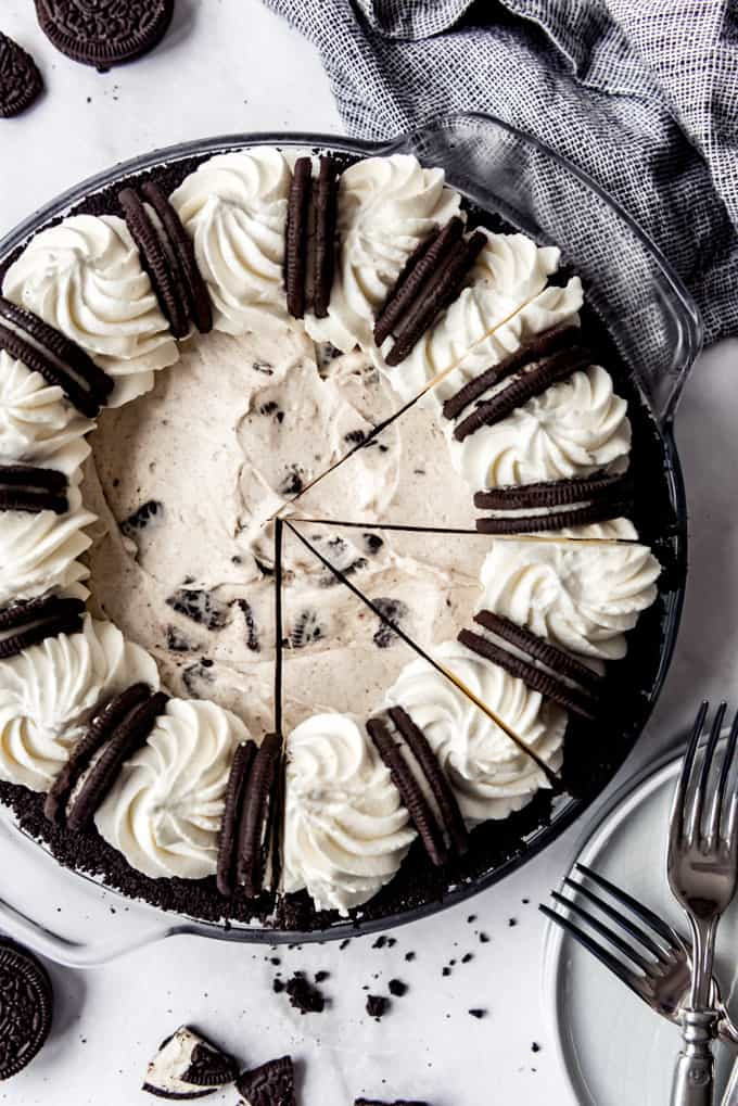 Overhead, Oreo cheesecake sliced and ready to serve, next to forks and cookies on surface.