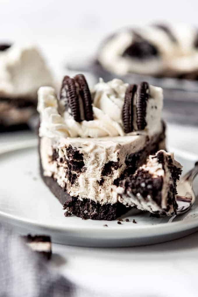 side view, slice of oreo pie on white plate with bite on fork.