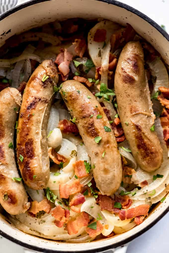 Sausages, onions, bacon, and potatoes in a pot.