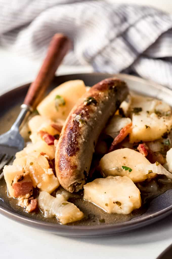A british banger on a plate with potatoes and onions.