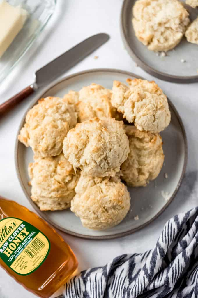 overhead, drop biscuits on a grey plate next to honey.