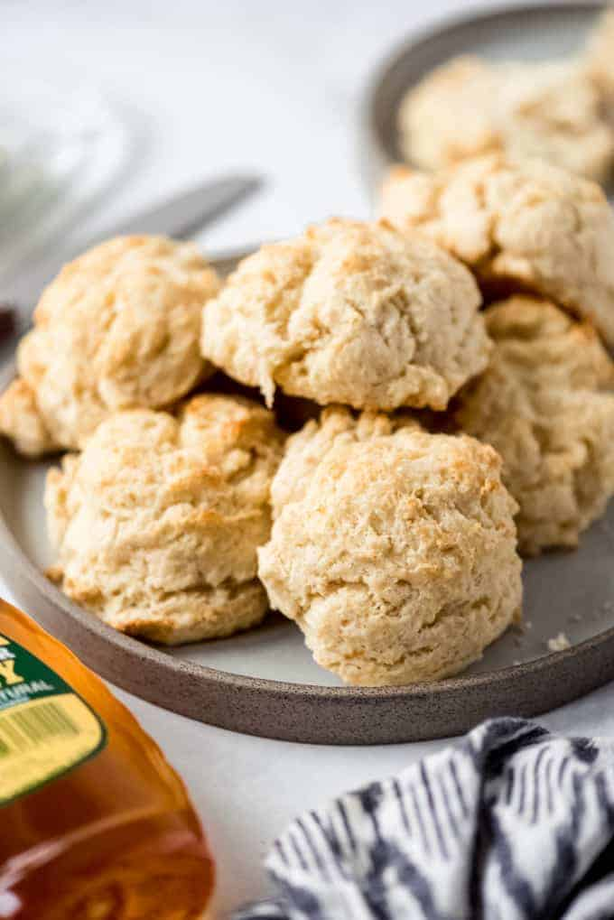 side view, drop biscuits on a grey plate next to honey.
