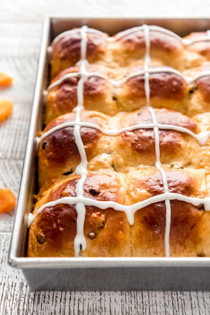 iced hot cross buns in a baking pan