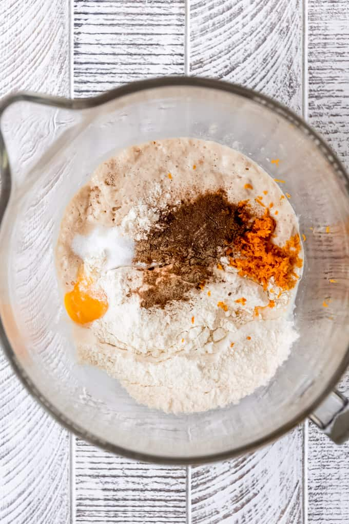 mixing flour, spices, orange zest, and eggs into a yeasted dough