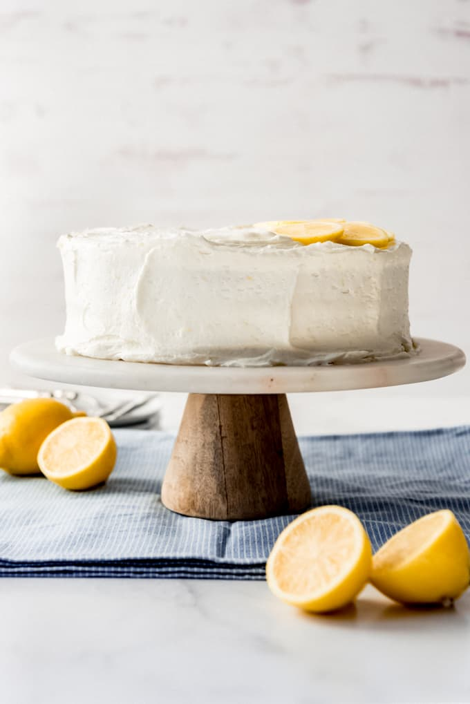 a frosted lemon cake on a cake stand