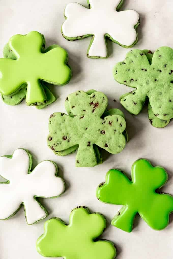 Stacks of mint chip cut out cookies in shamrock shapes.