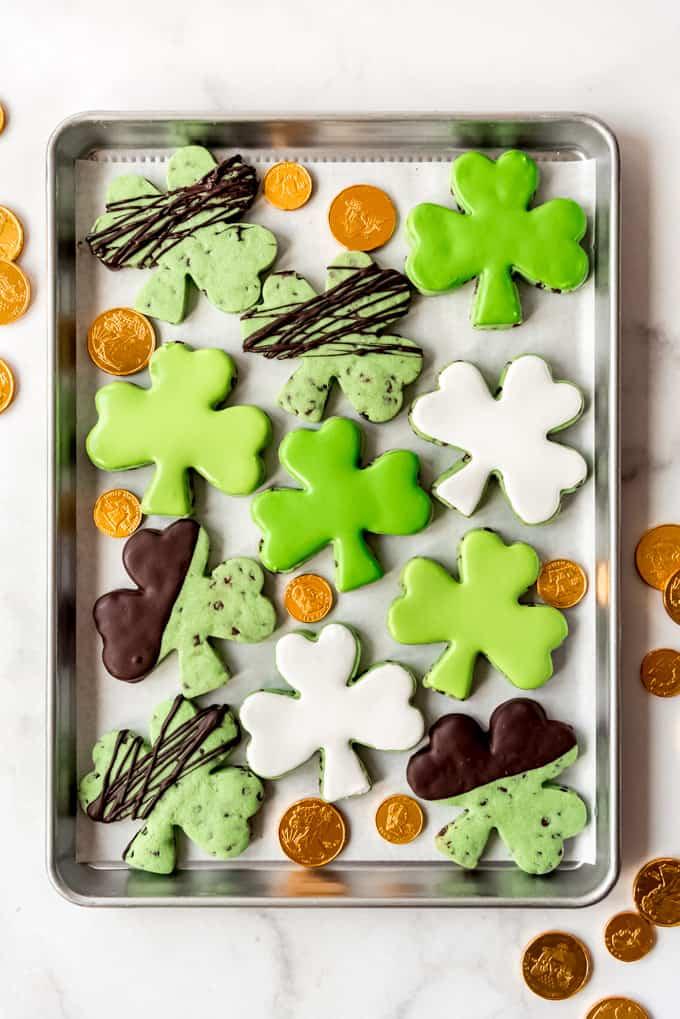 Decorated shamrock sugar cookies on a baking sheet.