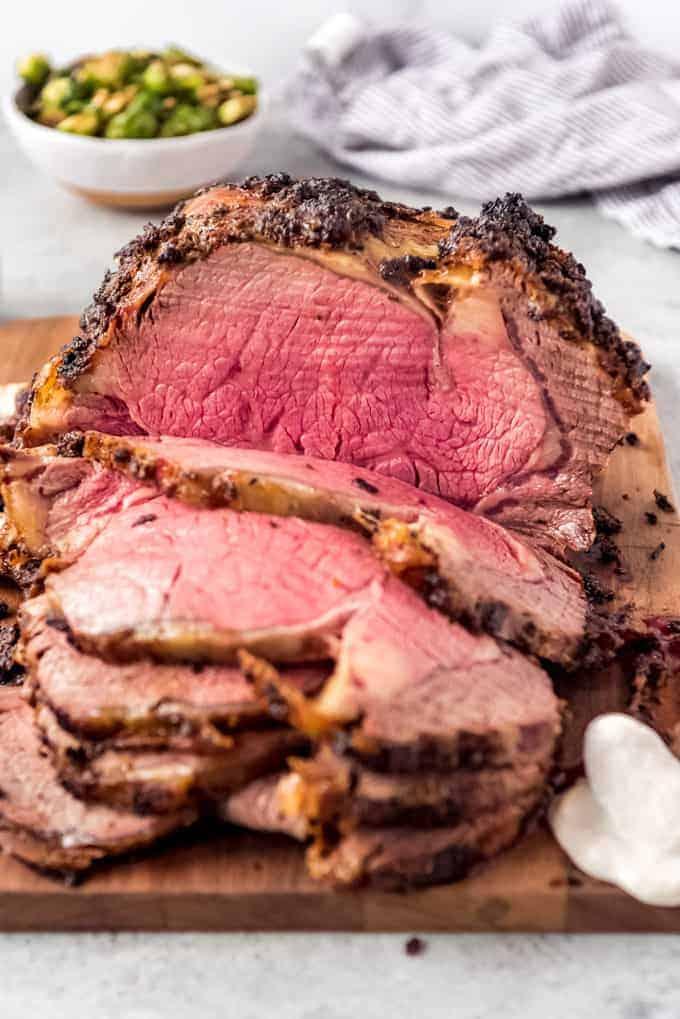 medium rare sliced prime rib roast on wooden board