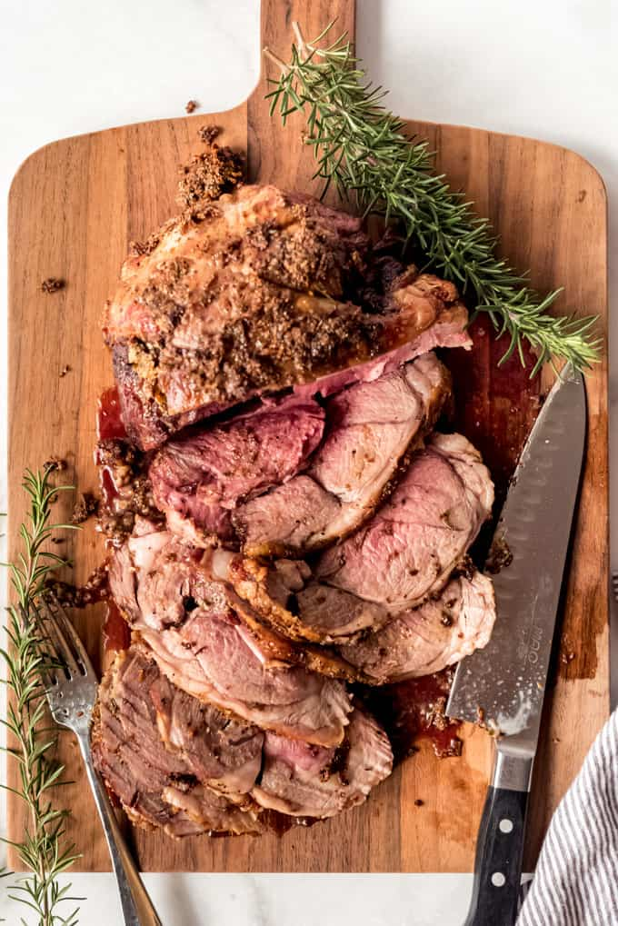 Boneless Leg of Lamb sliced to eat on wooden board, overhead shot