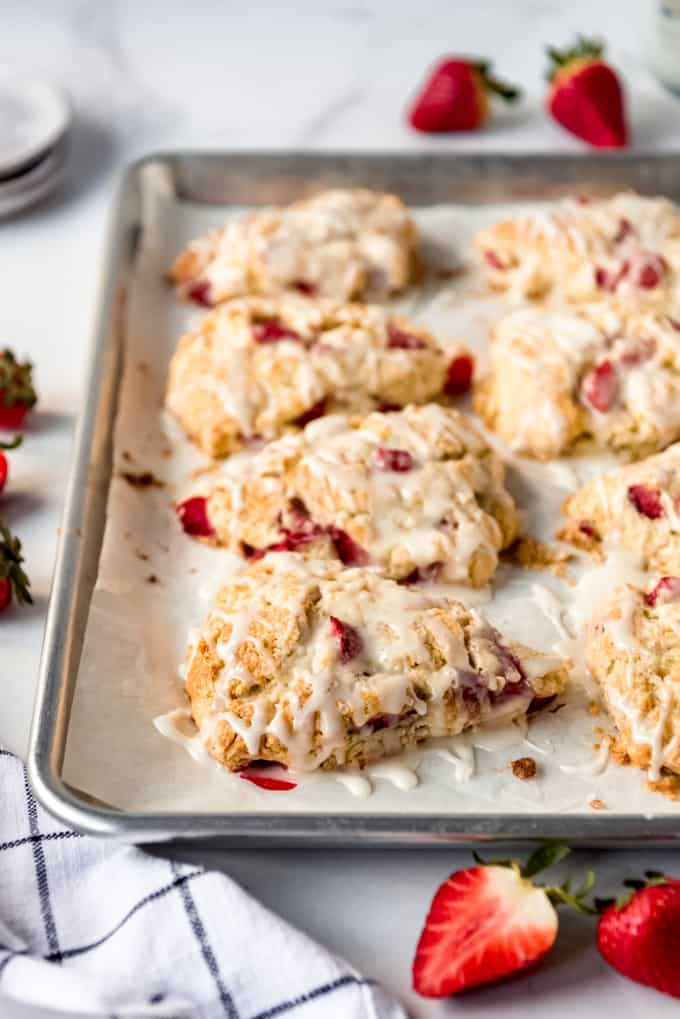 glazed strawberry scones on a baking sheet lined with parchment paper